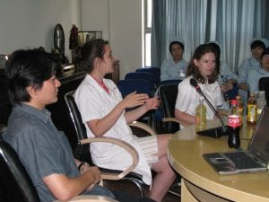Lab employees and PhD student giving presentation