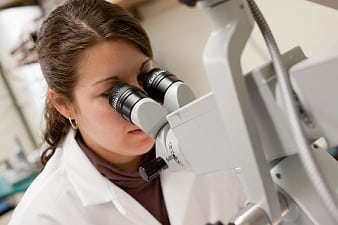 medical student looking at microscope